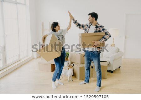 Young couple five high five to each other, carry big cardboard boxes during moving day, agree to wor Stock photo © vkstudio