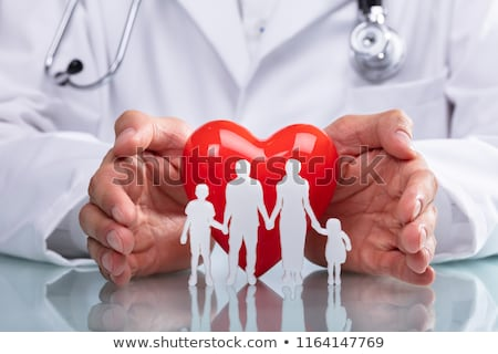 Doctor Protecting Red Heart With Family Figure Stock photo © AndreyPopov