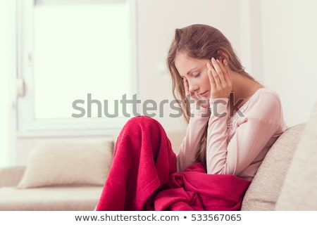 Woman with headache and migraine sitting in her apartment Stock photo © Kzenon