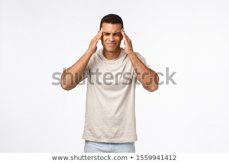 Handsome brazilian guy suffering terrible headache, grimacing from pain, squinting and touching temp Stock photo © benzoix