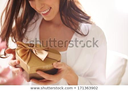 Beautiful woman with heart packed in a golden gift box Stock photo © ivelin