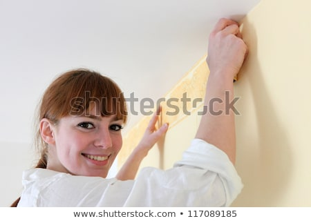 Female decorator hanging wallpaper Stock photo © photography33