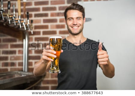 Smiling waiter in suit showing thumbs up stock photo © wavebreak_media