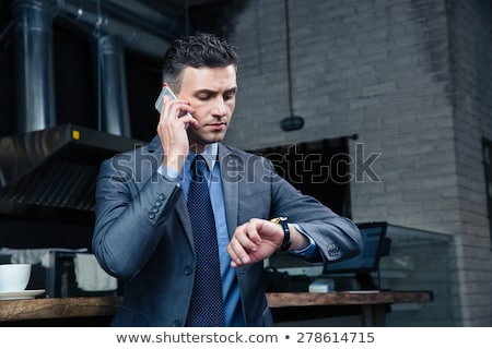 Man on the telephone checking watch Stock photo © photography33