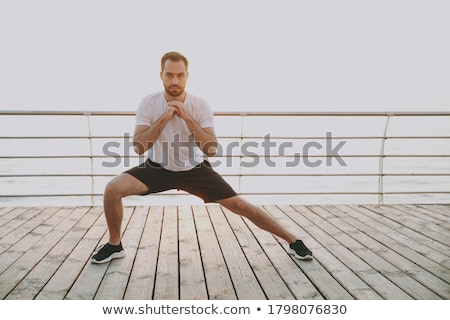 young bearded man squats outside Stock photo © feedough
