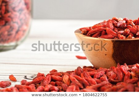 Stockfoto: Wooden Bowl Full Of Dried Goji Berries On The Table