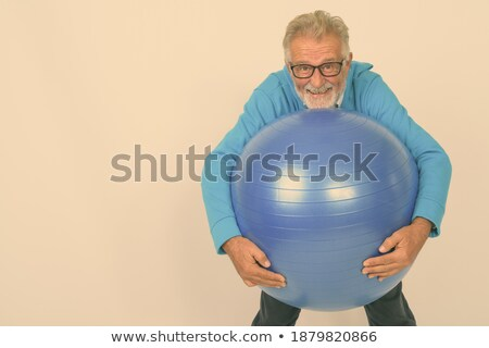 Portrait of senior man holding exercise ball while standing at beach Stock photo © wavebreak_media