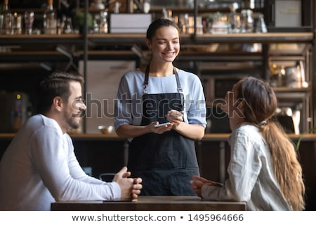 Waiter serving food to girl at a table Stock photo © IS2