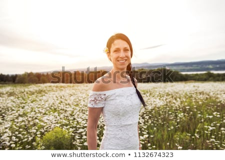 Young lovely smiling woman wonders ondaisy flower Stock photo © Lopolo