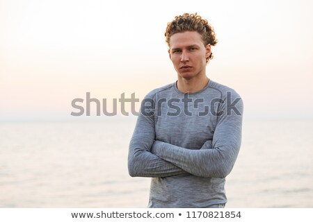Serious Curly Sportsman posing with crossed arms Stock photo © deandrobot