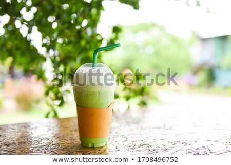 Green tea latte with ice in a plastic cup and straw and spoon with powder matcha on yellow backgroun Сток-фото © galitskaya