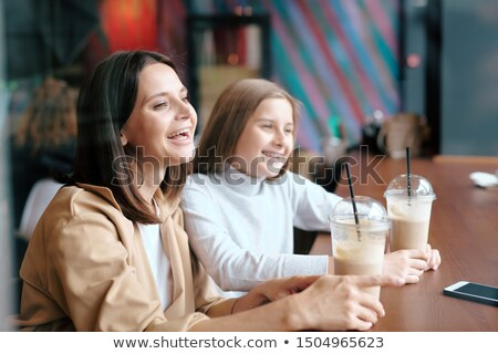 Ecstatic female and her pretty daughter with milk cocktails laughing in cafe Stock photo © pressmaster