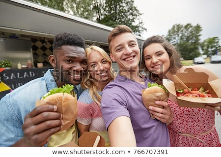 man taking picture of friends eating at food truck Stock photo © dolgachov