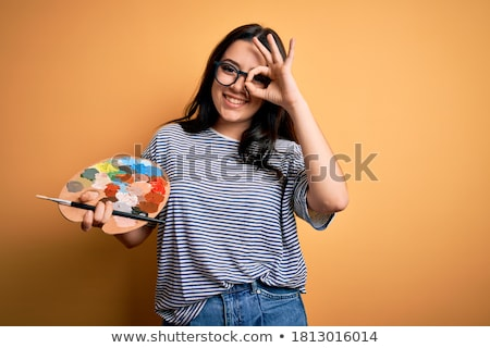 Happy and successful painter with palette looking at painting on easel Stock photo © pressmaster