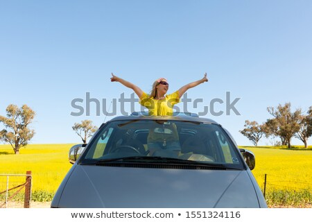 Happy woman standing out the sunroof of her 4wd car by canola fi Stock photo © lovleah