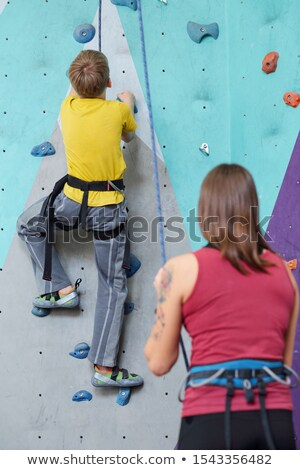 Back view of schoolboy in activewear moving upwards on climbing wall Stock photo © pressmaster