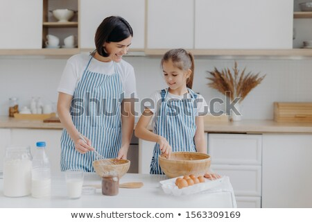 Indoor view of happy mother and daughter prepare tasty supper together, stand next to each other in  Stock photo © vkstudio