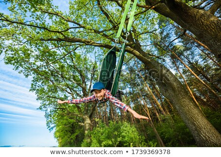 A child rides on a swing tied to a tree outdoors Stock photo © ElenaBatkova