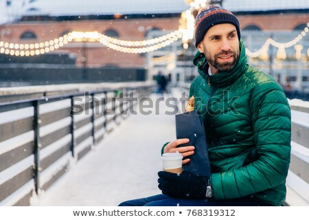 Middle aged man looks thoughtfully aside, has snack outdoors dur Stock photo © vkstudio