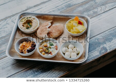 Traditional Israel food concept. Bowl of exotic dish on tray. Hummus, vegetables with spices. Pita b Stock photo © vkstudio