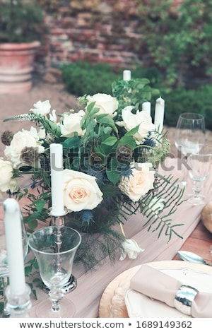 Candles and vase with white roses placed on round table near win Stock photo © dashapetrenko