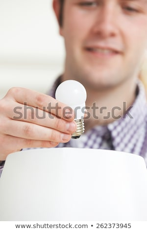 Man Putting Low Energy LED Lightbulb Into Lamp At Home Stock photo © HighwayStarz