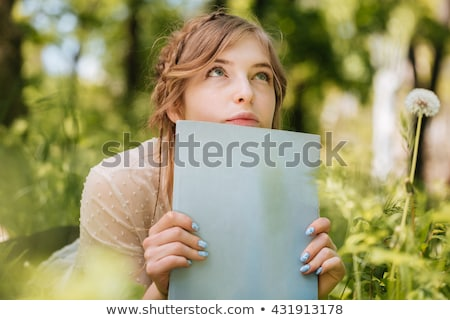 Pensive woman lying and reading magazine ourdoors Stock photo © deandrobot