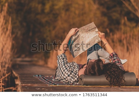 woman and man lying on reading map stock photo © is2