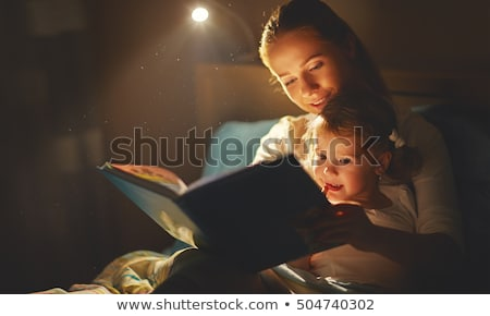 happy family reading book in bed at night at home stock photo © dolgachov
