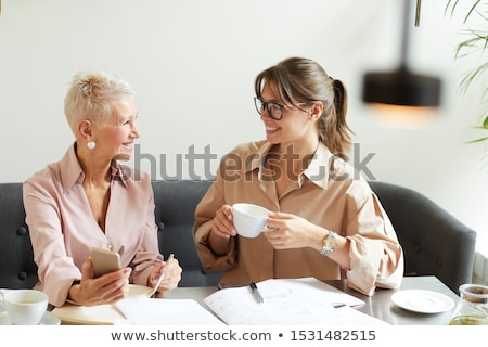 smiling mature businesswoman talking on the phone while she is s stock photo © boggy