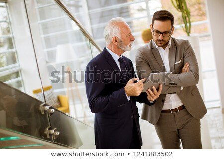 Stock photo: Senior businessman pointing and showing something to junior part