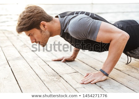 Sportsman outdoors at the beach make sport exercises. Stock photo © deandrobot