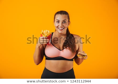 Image of joyful chubby woman in tracksuit holding sandwich and f Stock photo © deandrobot