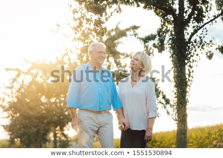 Couple of senior woman and man having an evening stroll Stock photo © Kzenon
