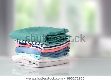Bright white clean clothes, laundry on blue background Stock photo © MarySan