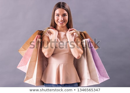 cheerful woman holding shopping bags isolated over grey background using mobile phone looking aside stock photo © deandrobot