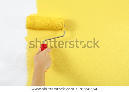 Woman painter painting a wall with yellow paint Stock photo © Kzenon