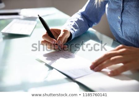 Zakenvrouw ondertekening cheque hand houten bureau Stockfoto © AndreyPopov