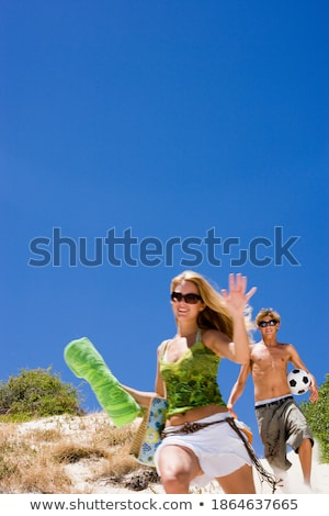 Young Couple Running Down Sand Dune On Beach stock photo © monkey_business