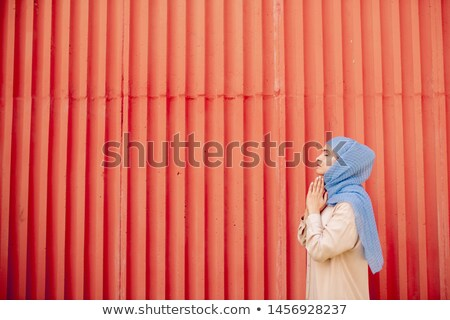 Young islamic woman in casualwear and hijab praying against red wall Stock photo © pressmaster