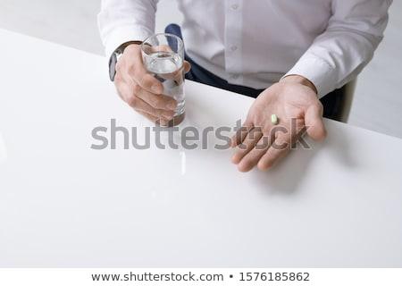Elegáns üzletember fehér póló tart üveg Stock fotó © pressmaster