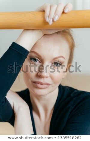 Close up shot of restful woman with ginger hair, has make up, looks at camera, has serious expressio Stock photo © vkstudio