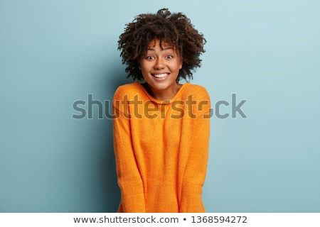 Smiling optimistic curly female with pleased facial expression, keeps hands on rim of spectacles, ha Stock photo © vkstudio