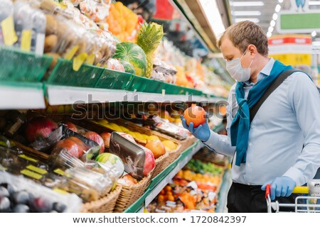 Sideways shot of man chooses fresh fruit to increase immunity during coronavirus outbreak, holds rip Stock photo © vkstudio