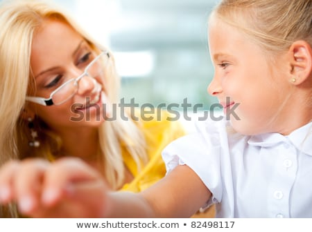 young pretty teacher helping to her students to make exercise in stock photo © hasloo