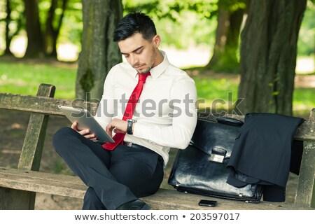 Işadamı oturma bank cep telefonu tablet iş Stok fotoğraf © jakubzak