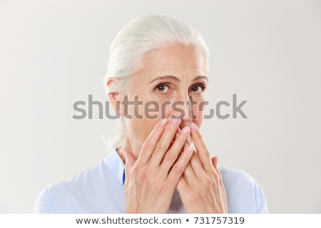 Mature woman with hand over her mouth Stock photo © bmonteny