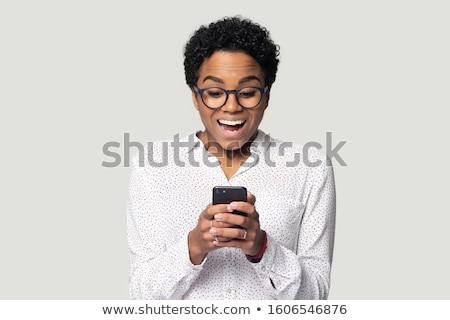 Young astonished woman holding a cellphone on white background studio Stock photo © ambro