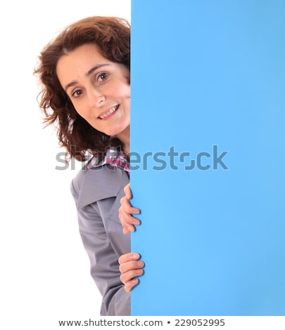 Young woman looking around the corner on white background stock photo © uleiber