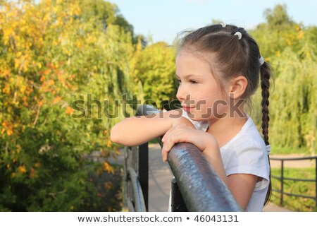 little girl is lean elbow on bridge fence and looking forward stock photo © paha_l